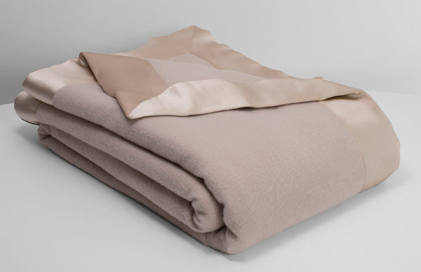 Henry cashmere and lambswool blend blanket in champagne beige lying neatly folded with an off white background