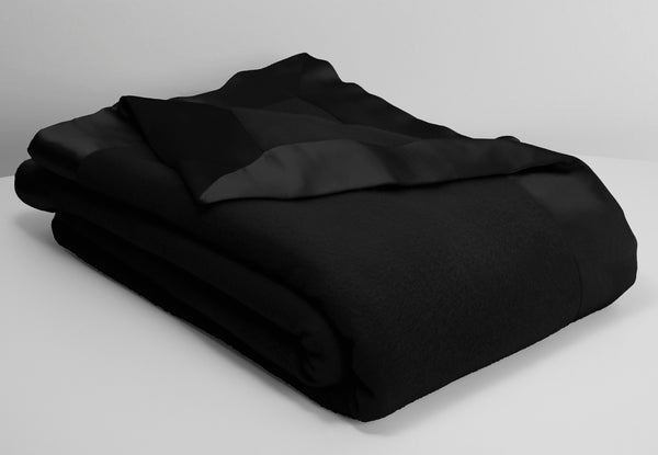 hollywood ava luxury cashmere and lambswool blanket in black lying neatly folded with an off white background