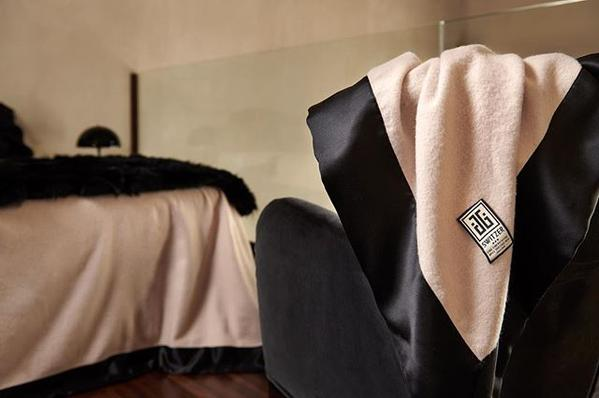 Close up of the camille cashmere blend blanket with pure black silk 4 inch borders hanging off a chair with a bed in the background