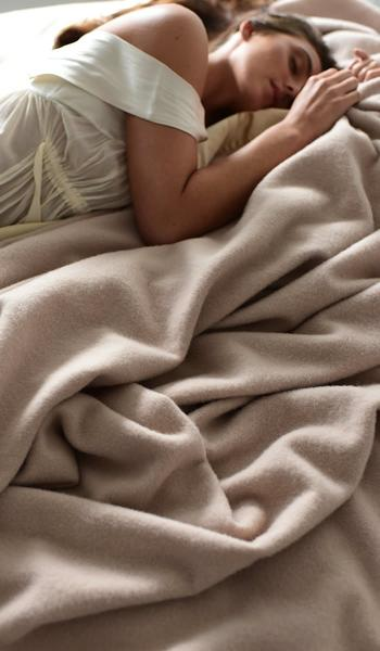 model in bed with hollywood ava luxury blanket in champagne beige
