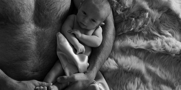 black and white photo of man in bed with baby with luxury blankets by JG Switzer