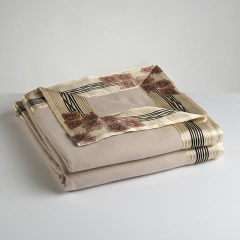 Now Voyager luxury throw blanket in champagne beige lying folded with signature gold rose motif borders.