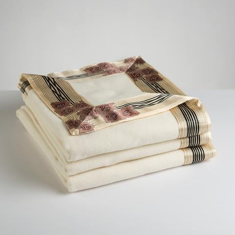 Now Voyager luxury throw blanket in white lying folded with rose motif pure silk border