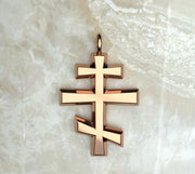 Rose gold or rose gold plated round beveled three bar orthodox cross.
