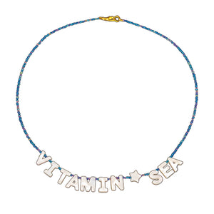 "tropical style beach necklace that reads ""vitamin sea"" in mother of pearl and seed bead strand"