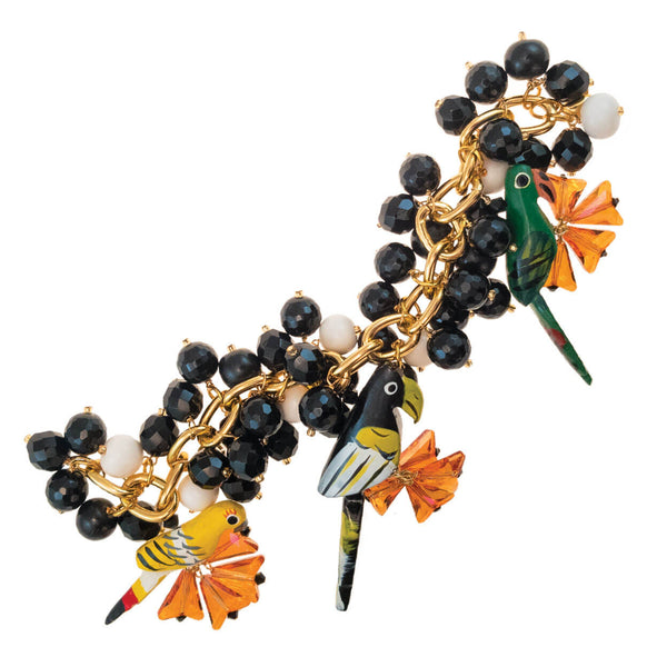 tropical style gold charm bracelet with three parrots in green, yellow and black with orange swarovski crystal and black and white bone charms