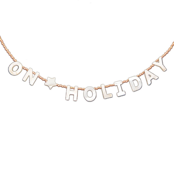 "beach inspired necklace that reads ""on holiday"" with mother of pearl letters on seed bead strand"