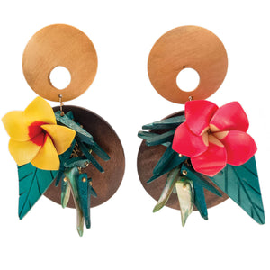 tropical pink and yellow flower earrings on wood with green leaves and coco sticks with mother of pearl