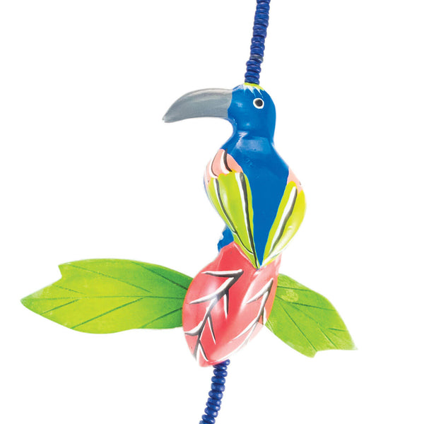 up close of tropical necklace with blue and green vintage toucan on blue wood bead and green stone strand.
