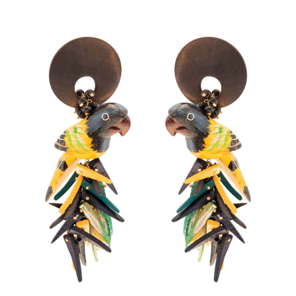 tropical inspired large earrings with yellow and black parrots hanging from brown wood and yellow, black, green coco stick and mother of pearl charm bottoms