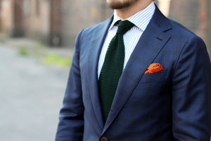 Blue suit with green knitted tie