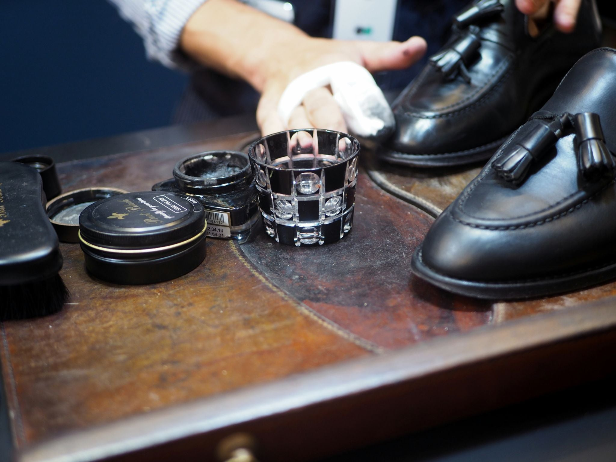 DLA Black shoes guide - My black tassel loafers getting treatment at the Boot Black booth at Pitti Uomo.
