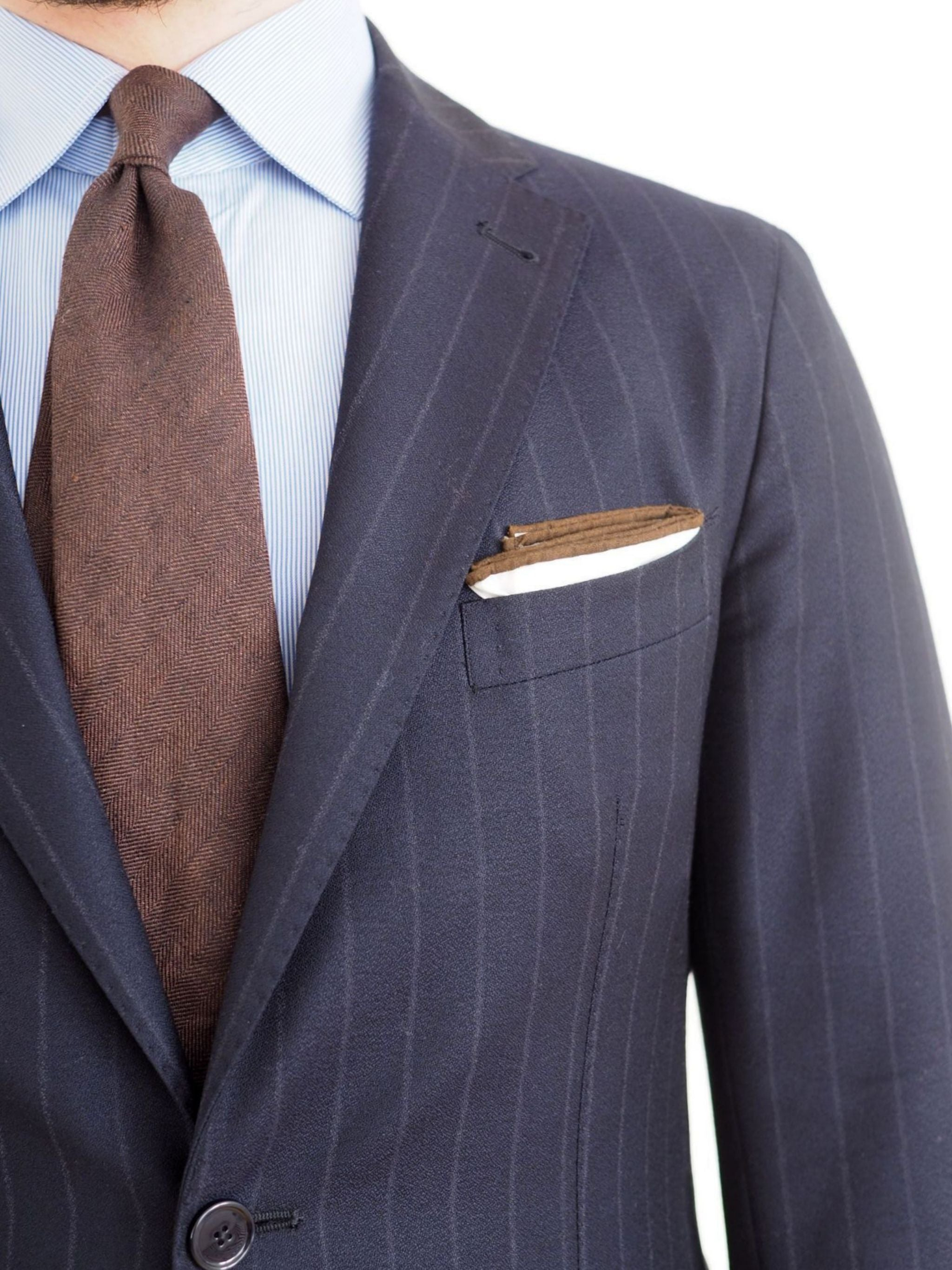 Dark blue chalk stripe suit with brown tie and cotton pocket square - close-up
