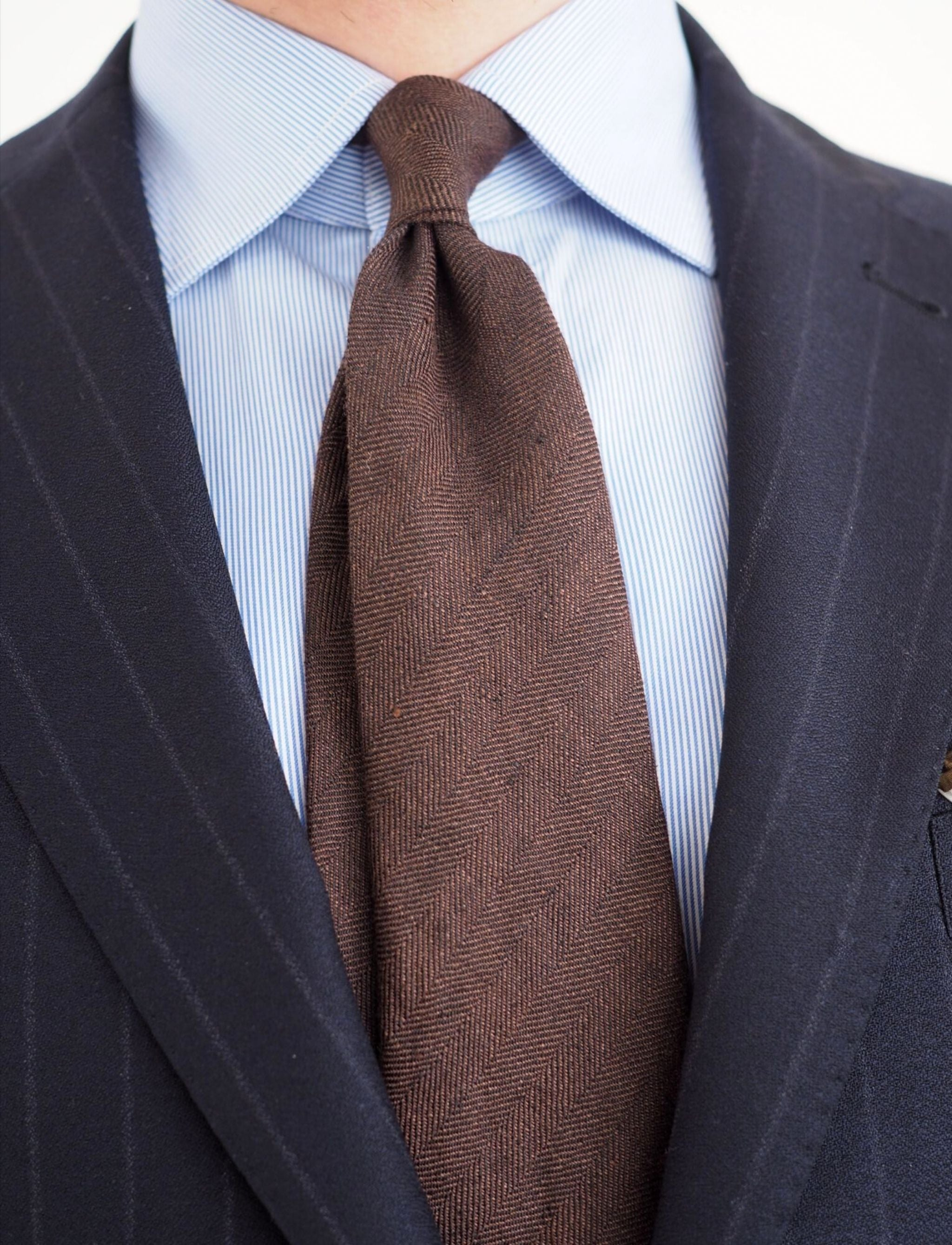 BLue chalk stripe suit with brown tie and double dimple.