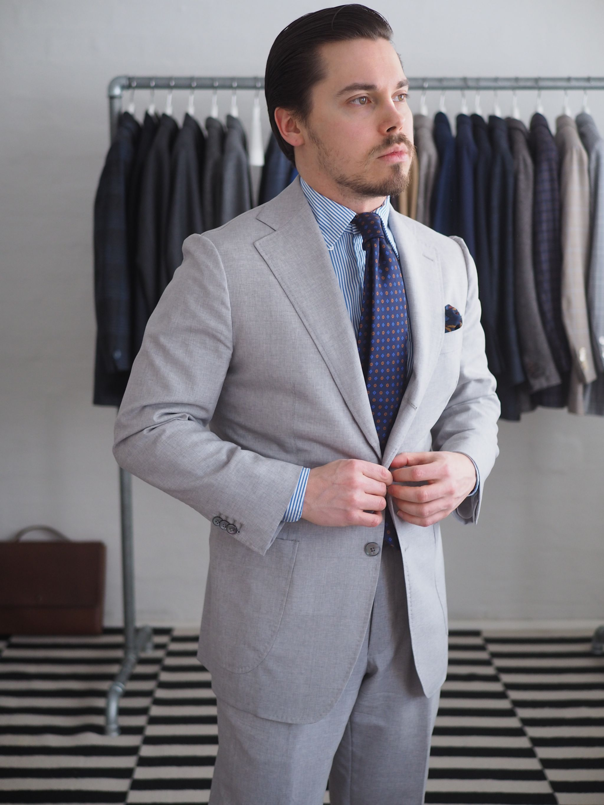 Light gray suit with a printed tie and striped shirt.