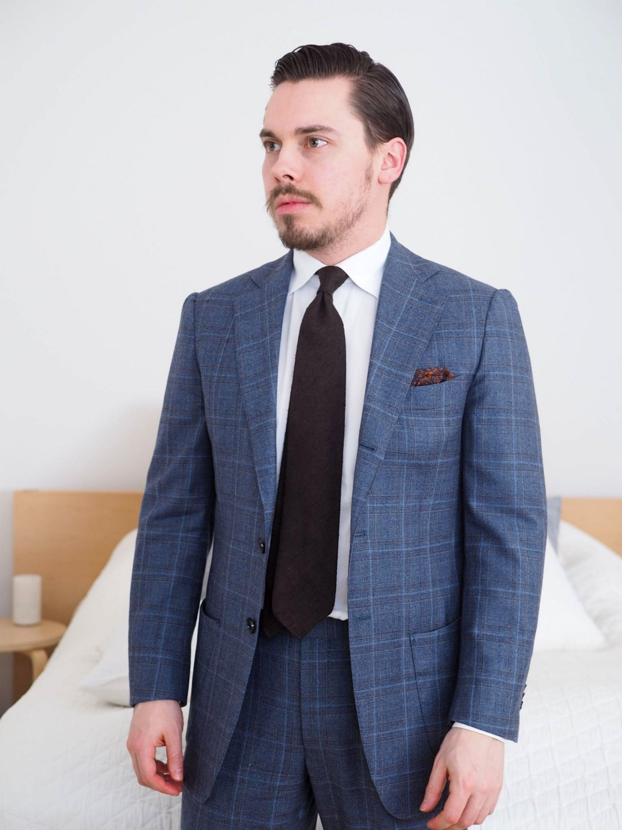 Light gray suit with restrained check pattern and neapolitan shoulder structure.