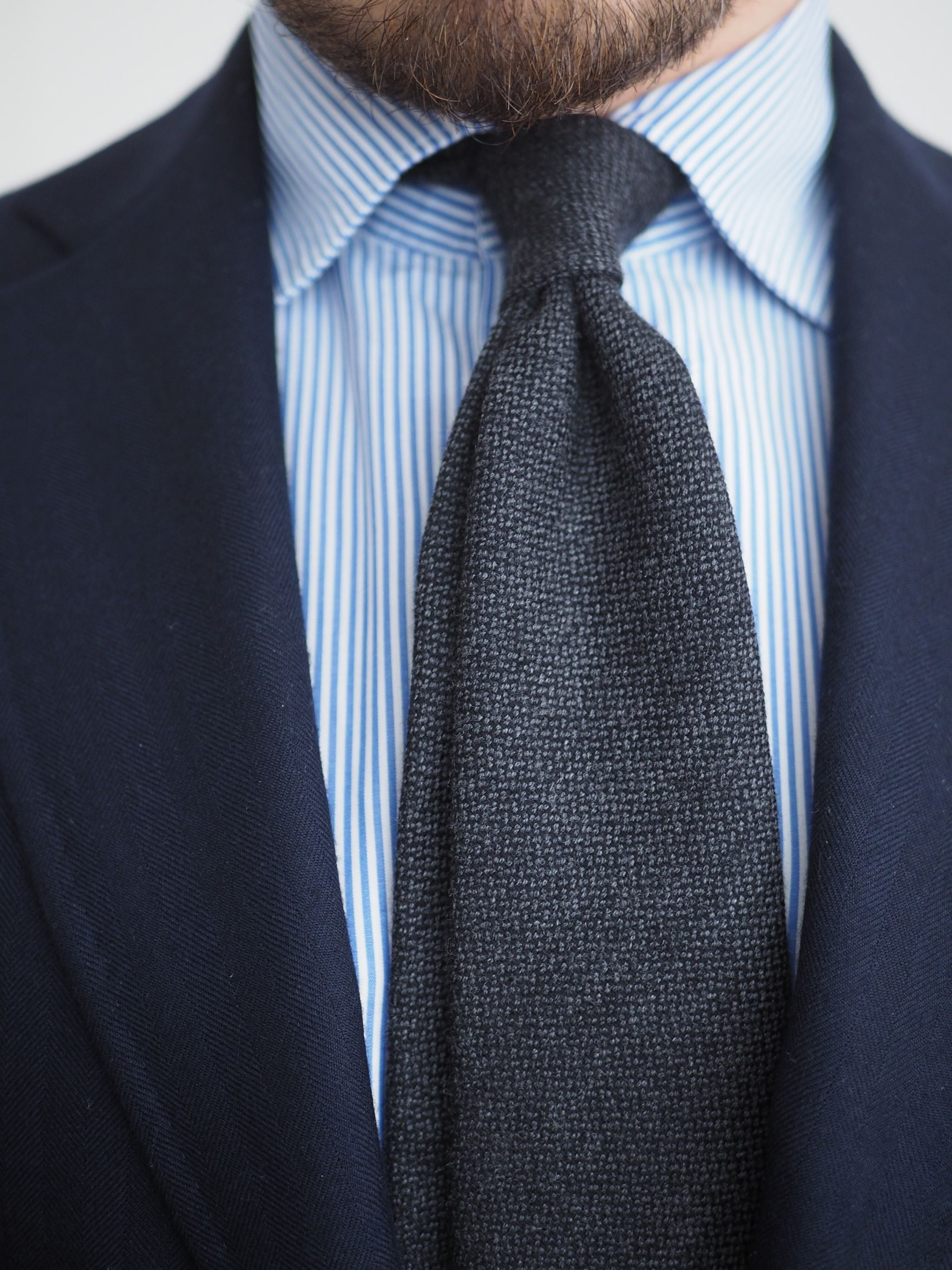 Blue suits - Close-up of the dark gray wool tie and four-in-hand knot.