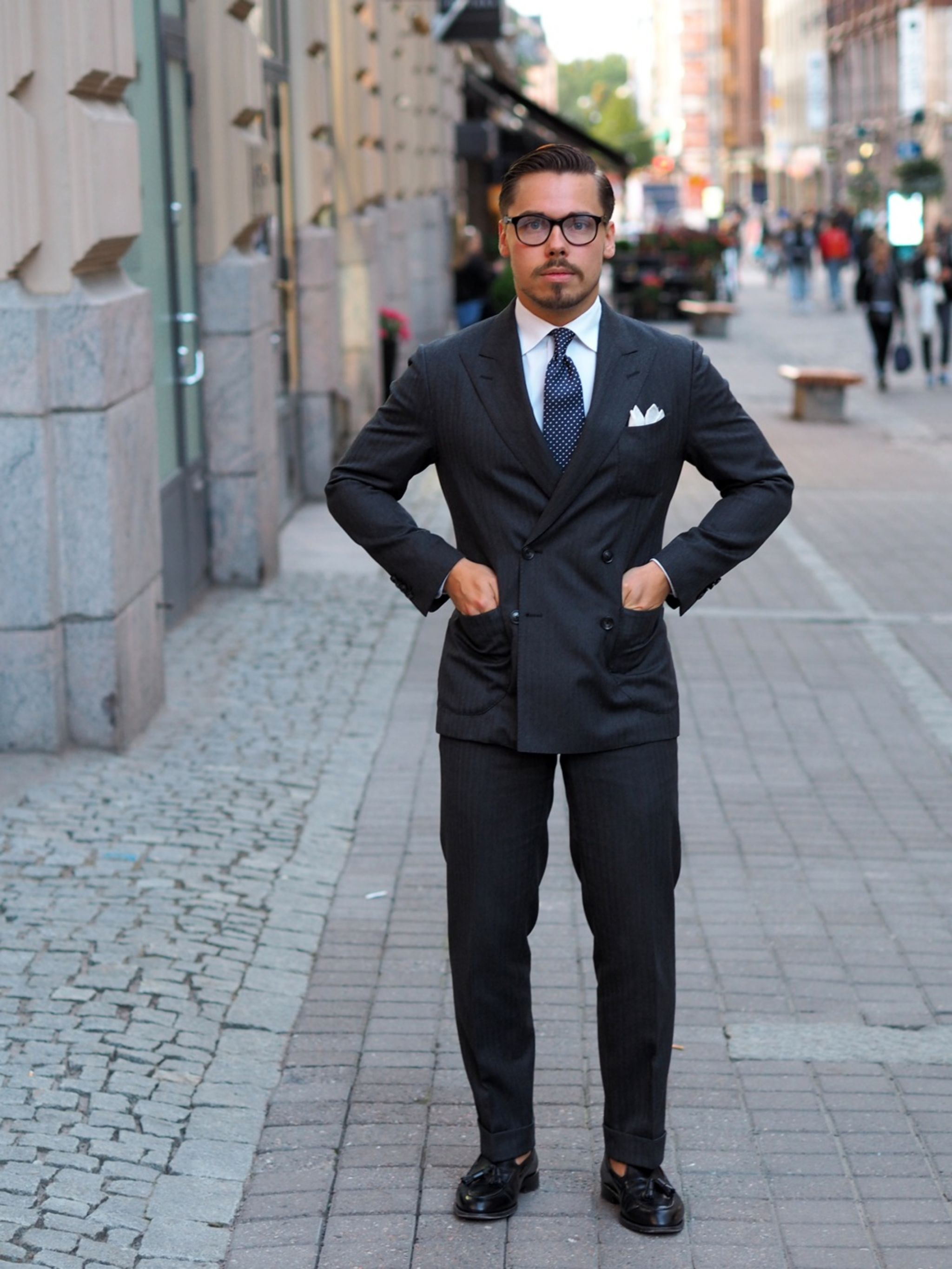 The navy blue pin dot tie - full shot with gray suit and black tassel loafers