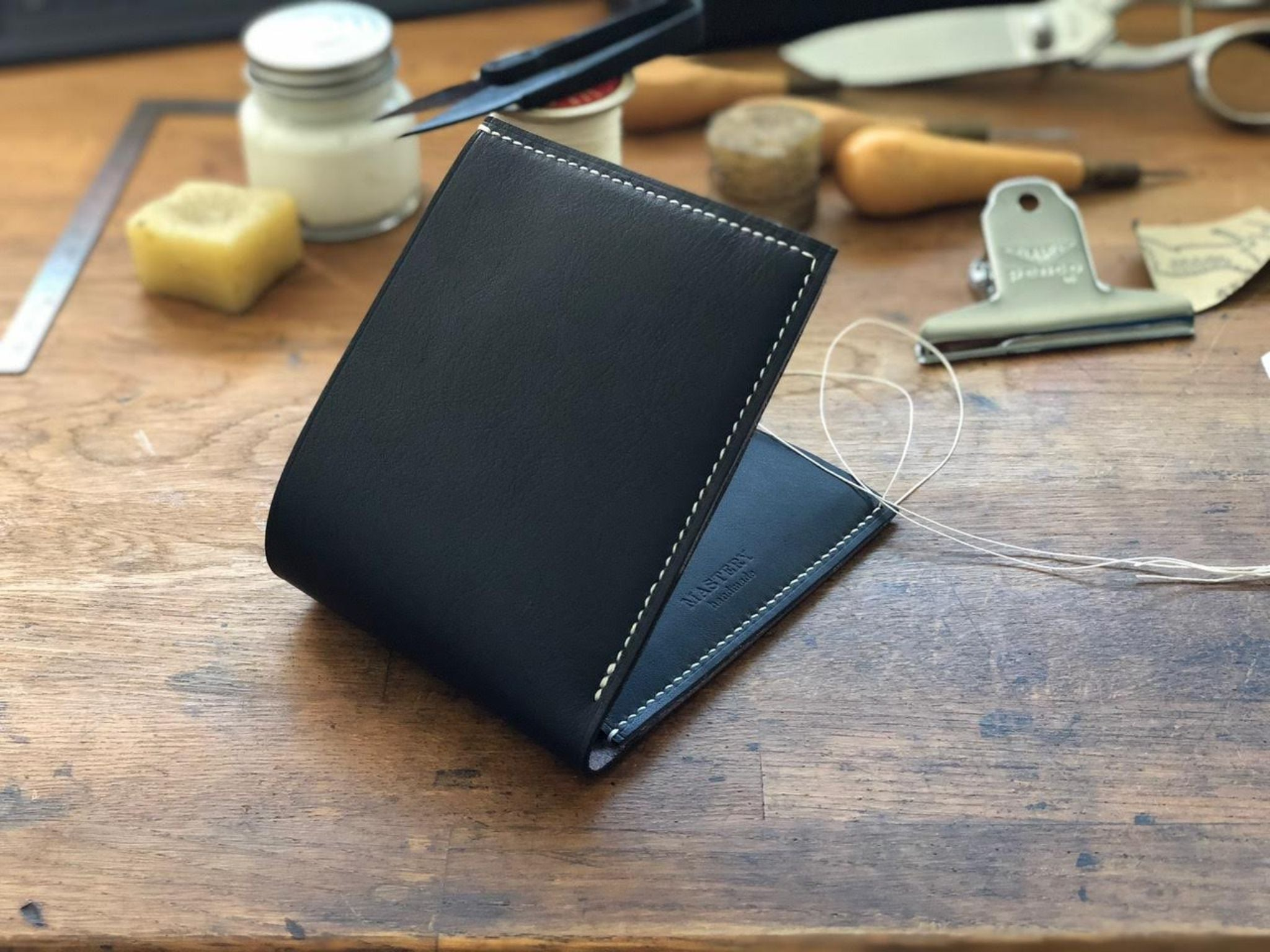 Hand-stitching the handmade wallet by Mastery co