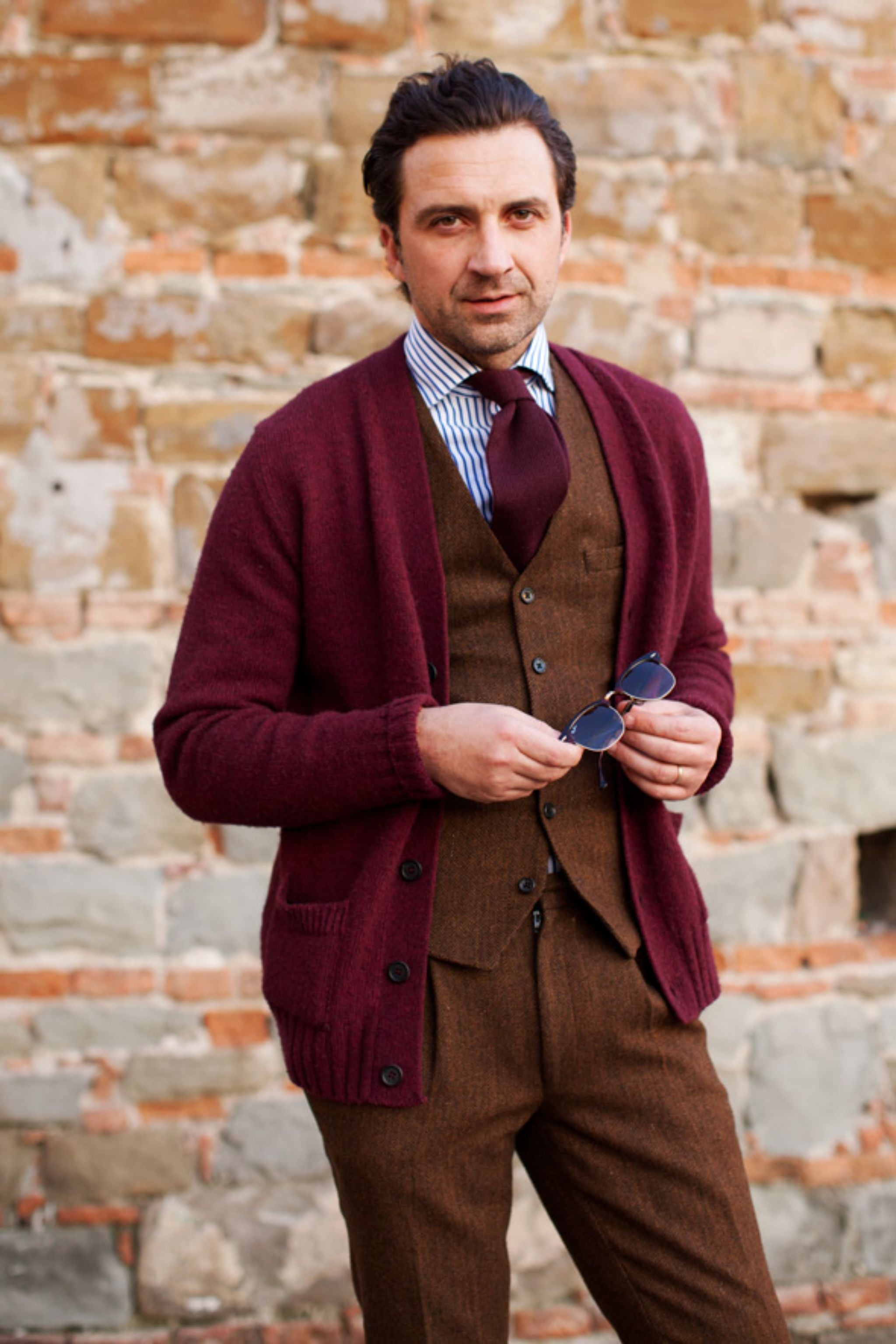 How about dressing down by replacing your three-piece suit jacket with a cardigan? Inspiring color-play with the tones of brown and burgundy. Pic by The Sartorialist.