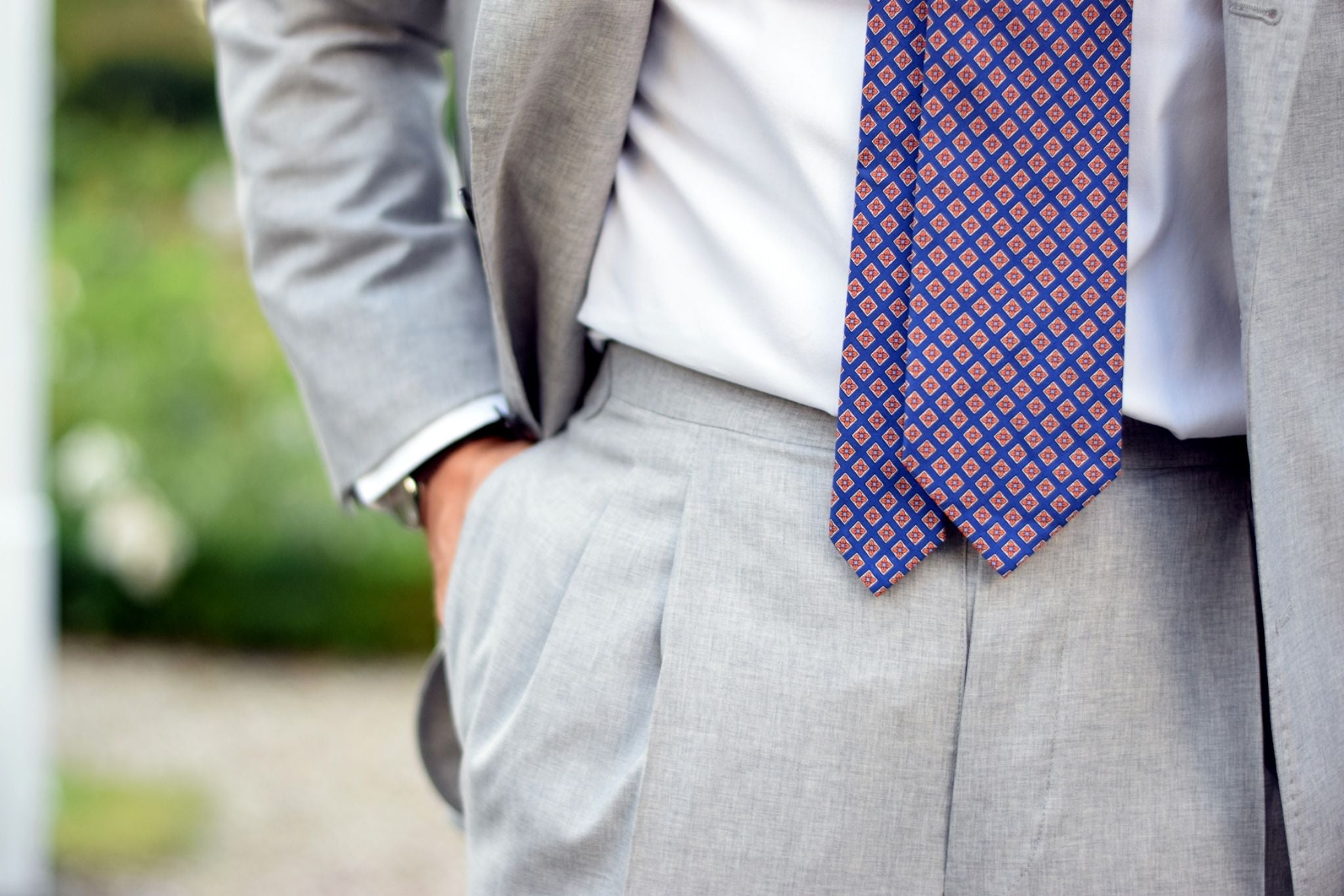 Light gray suit with orange accessories - tie details and double-pleats
