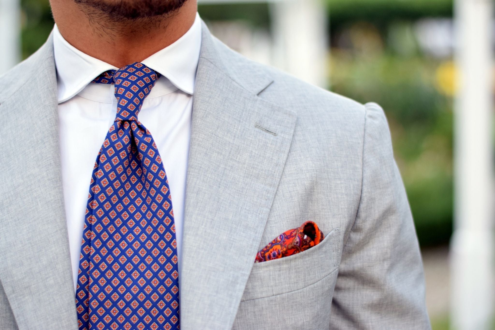 Light gray suit with orange accessories - floral print silk tie close-up and shoulder details