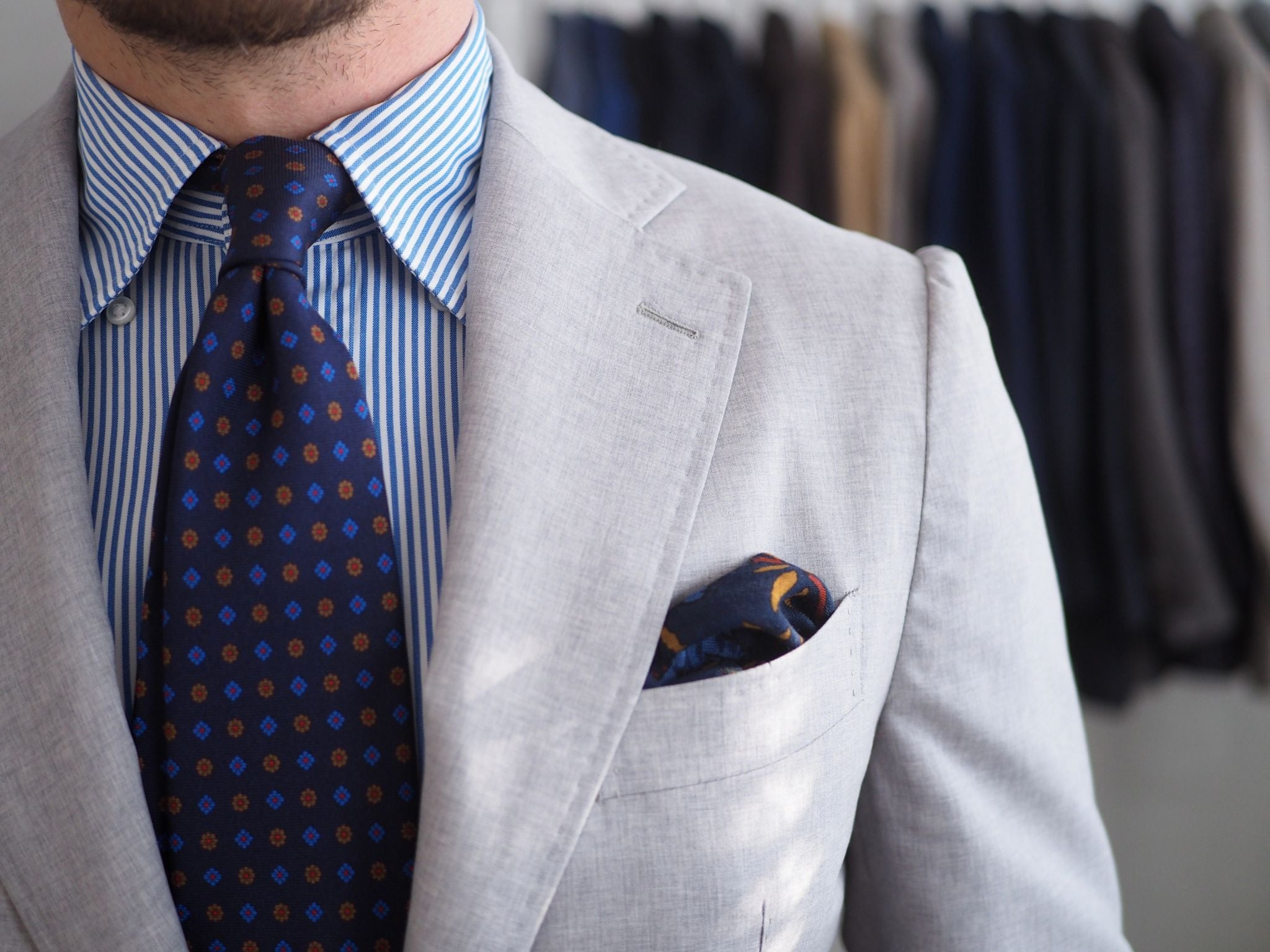 Printed silk tie with striped shirt and gray suit - close-up