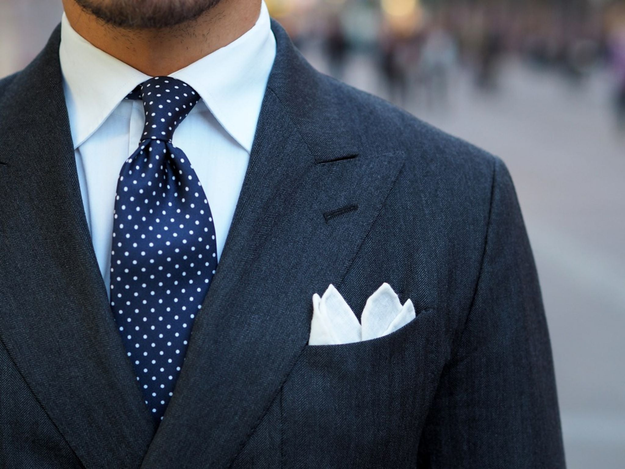 The navy blue pin dot tie - details with double-breasted herringbone suit and white linen pocket square