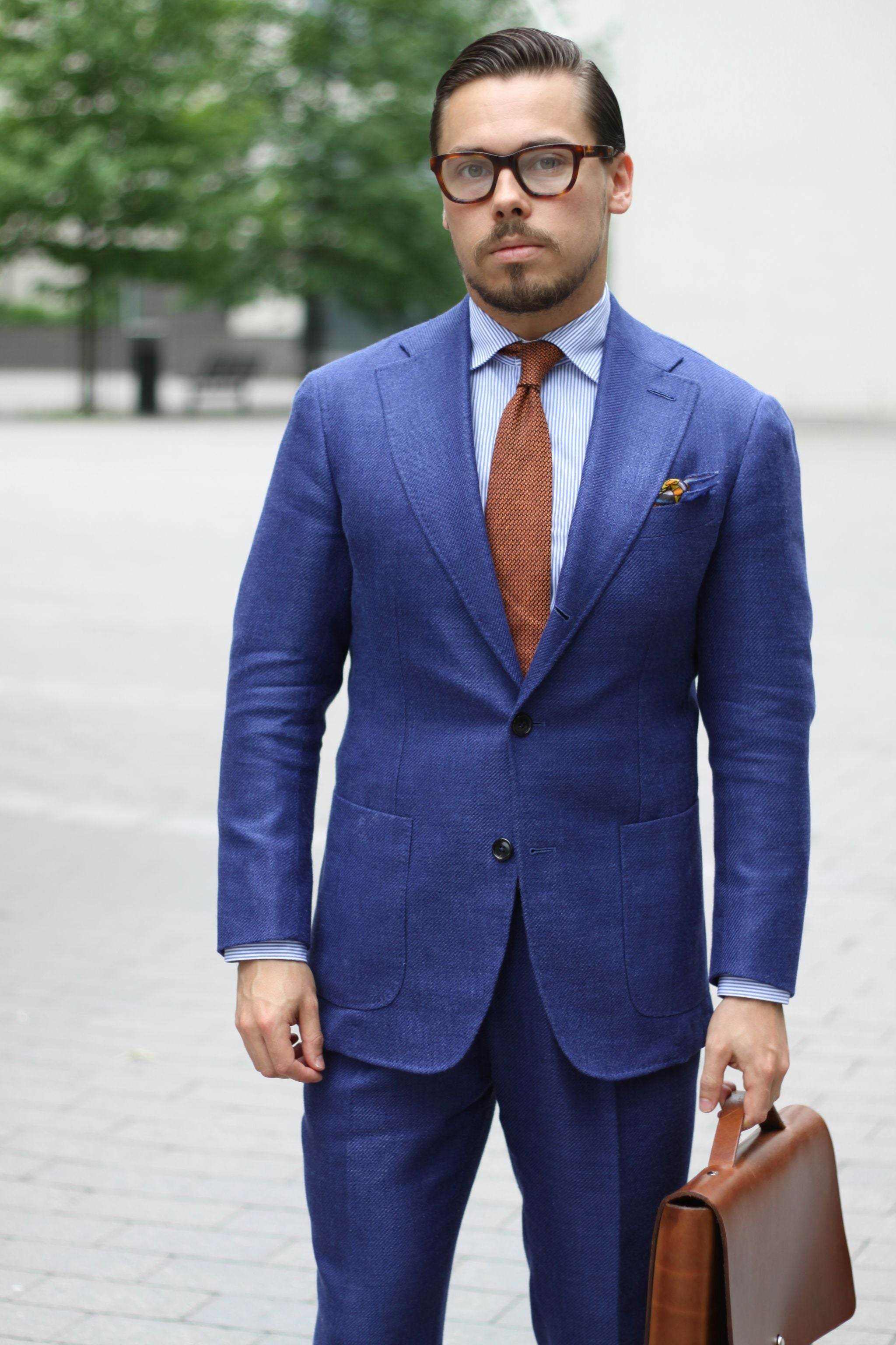 Navy blue suit with orange tie and striped shirt