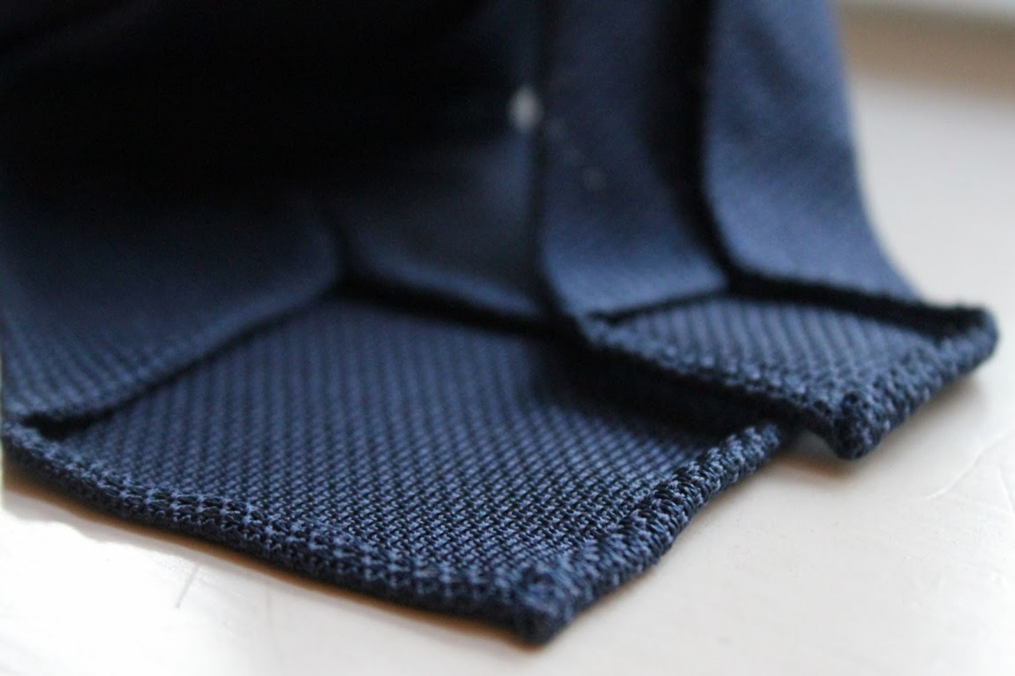 Navy grenadine bespoke tie details - untipped and hand-rolled edges
