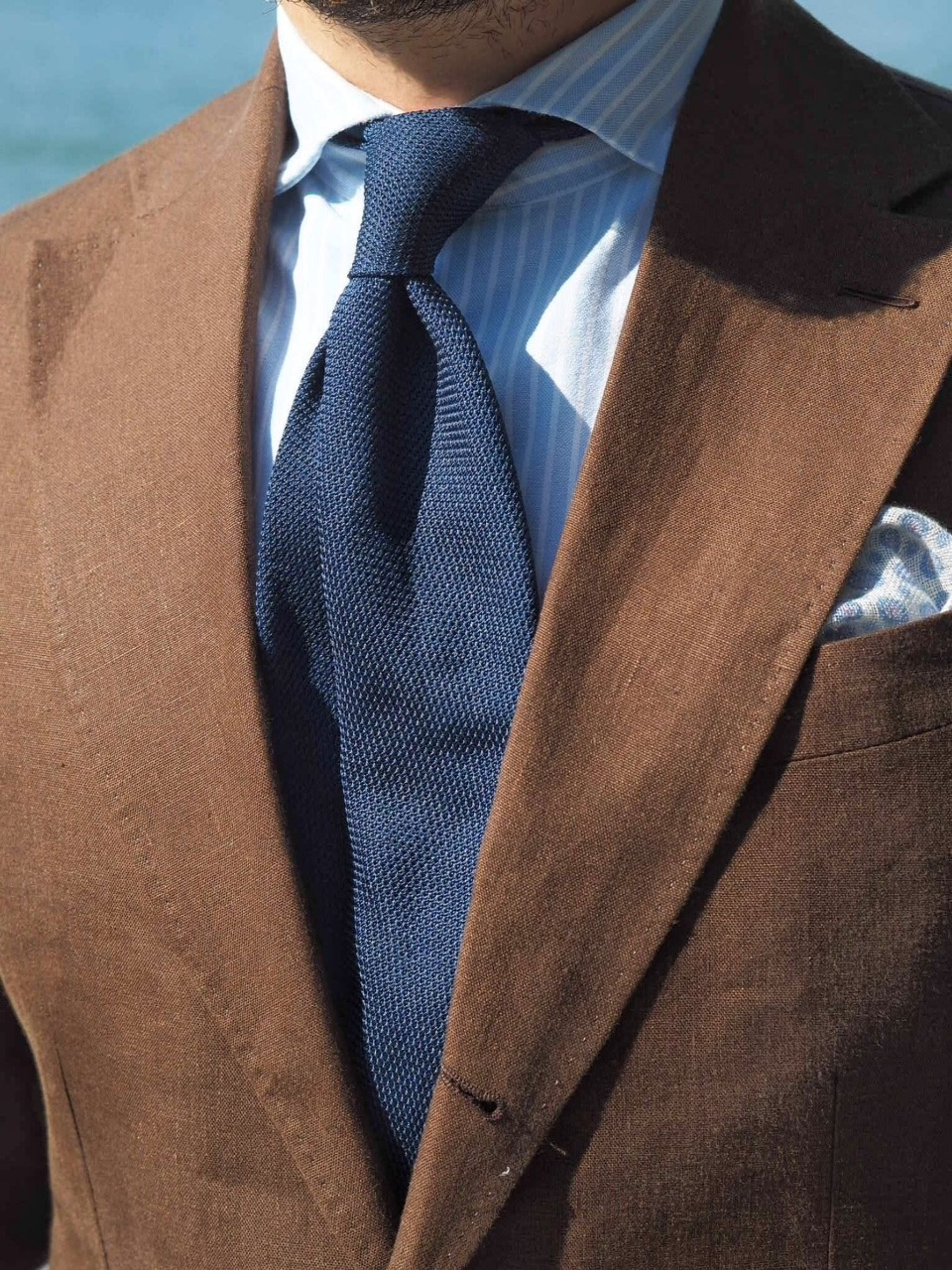 brown linen suit with navy grenadine tie details