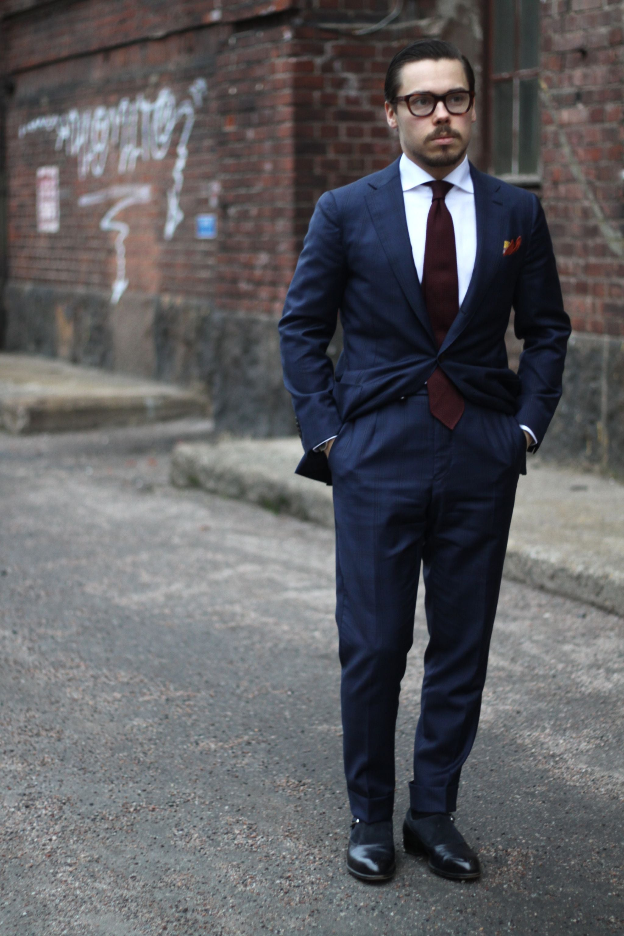 Dark blue suit with white shirt and burgundy tie is classic business attire.