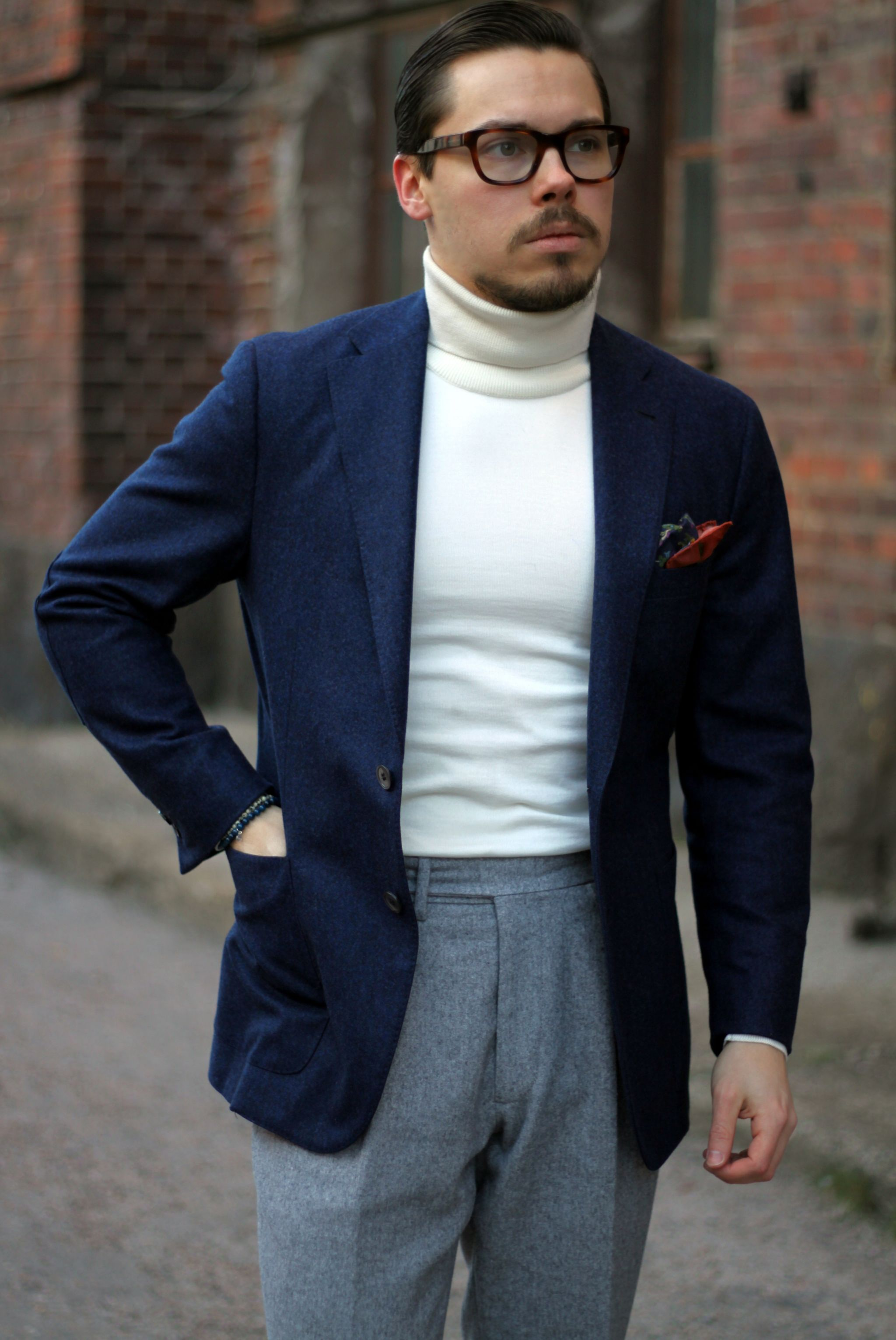 Navy blue blazer with off white roll neck sweater and gray flannel slacks.