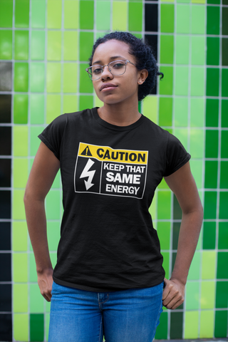 1222 Design: Woman wearing a black t-shirt with the phrase: CAUTION: Keep That Same Energy