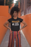 Beautiful Black woman standing front of a walkway with orange walls. Hands on hips, wearing orange stripped pants and a black t-shirt with the phrase  with the phrase: WARNING Clapbacks Loaded. The print is white and orange resembling a safety sign.