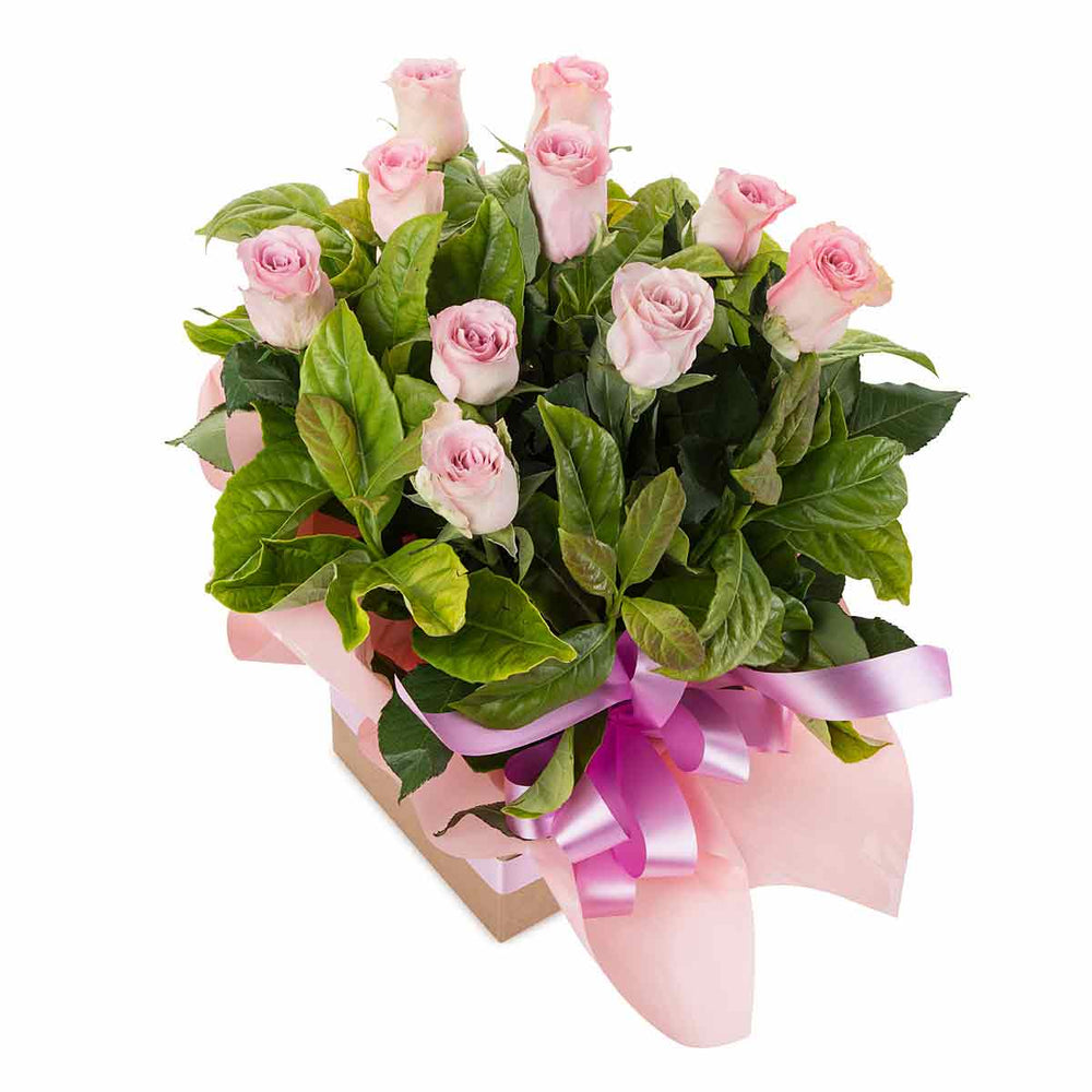 Pink roses and green leaves in a box with a pink ribbon
