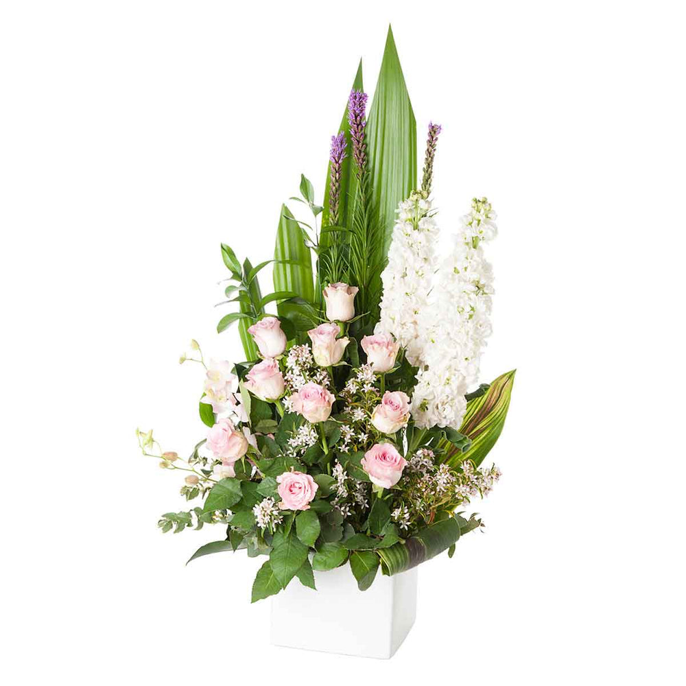 Pink and white flowers arranged in a white ceramic