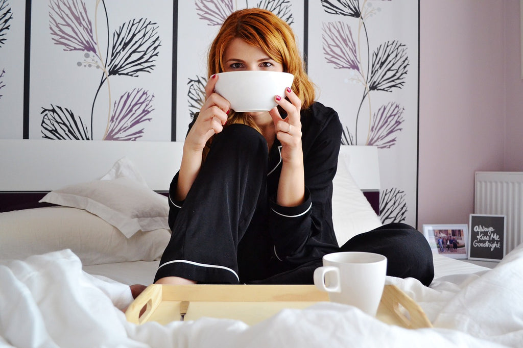 Woman in bed enjoying a low-carb breakfast