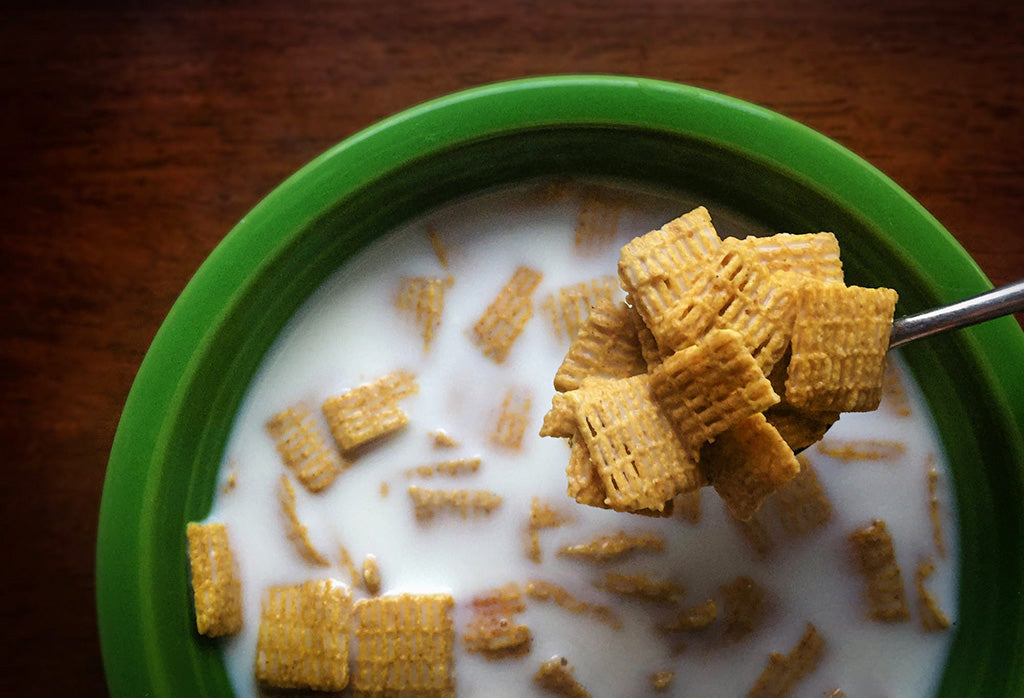Green bowl of cereal with milk