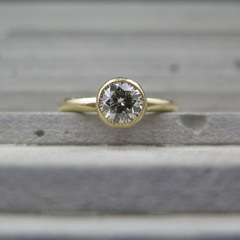 Round Brilliant Diamond bezel set with milgrain edge in yellow gold.