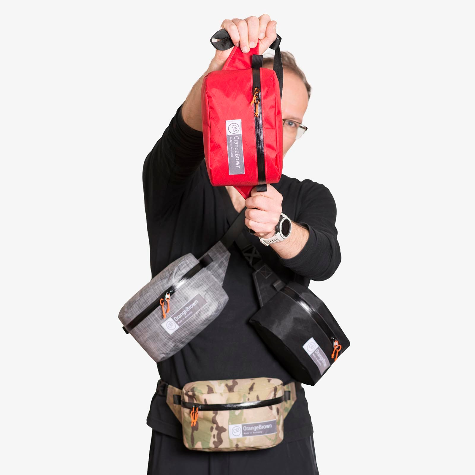 Four fanny packs for hiking and walking are held for presentation by one person.