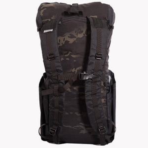 Backpack OB 36 made from X-Pac fabric by OrangeBrown. Rear view of pack with wide padded shoulder straps and sternum strap including emergency whistle. Colours are multicam black and black.