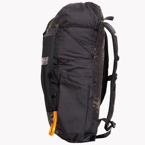 Backpack OB 36 made from X-Pac fabric by OrangeBrown. Side view of pack showing orange webbing loop for fixing hiking poles. Side pocket and compression cord adjustable with Line Loc. Colours are multicam black and black.
