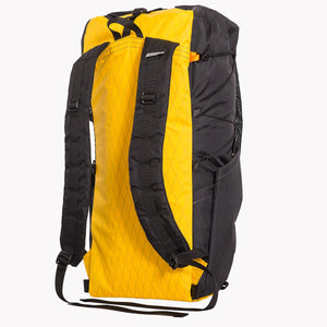 View of the shoulder straps and side pocket of a 36 L backpack. The back panel is yellow and the sides are black, both made from X-Pac fabric.