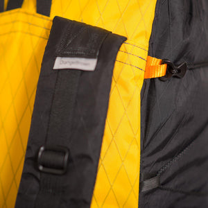 Detail view of a LineLoc 3 with a black 2.5mm cord running through it for the compression of a backpack. LineLoc3 is hold in place by an orange webbing loop.