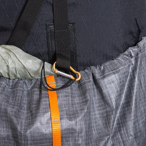 Detail view of front strap fixture which is used to hold the rolled top part of the pack into place. It has a provision for a small carabiner or cord so items can be secure within the front pocket.