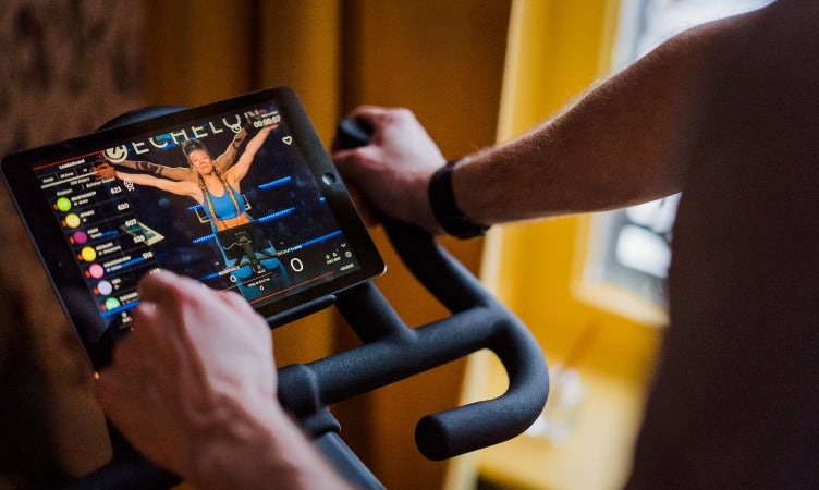 Someone exercising on a Sport S bike following an Echelon trainer's instructions on a tablet