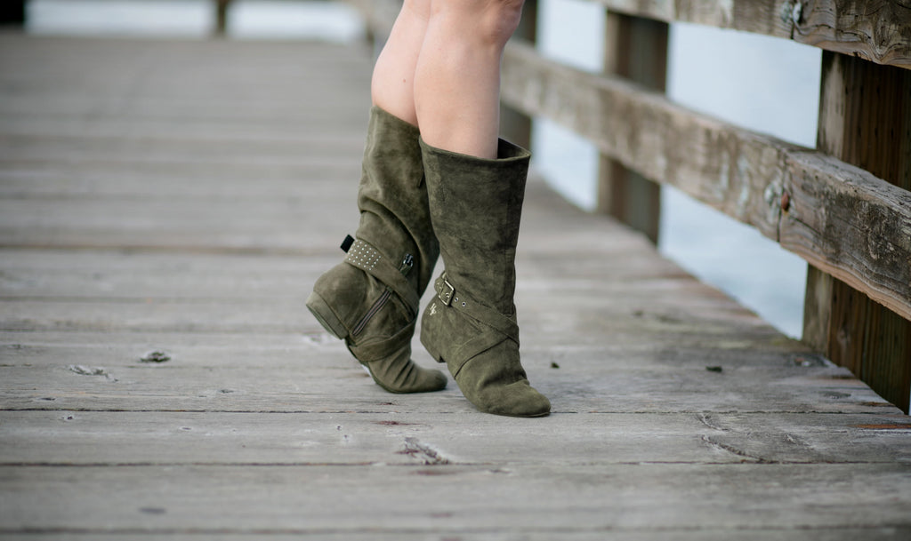 Aurora dance boots dark/olive green pair folded up in action, on wooden dock background