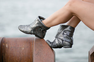 Aurora dance boots silver metallic pair folded down, side angle on ocean background
