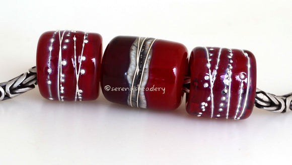 Red Hot Tube Beads Size: 11x13 & 15x13 mm Amount: 3 Beads Hole Size: 5 mm Two matching translucent red fine silver decorated tube beads and one red two-toned bead with silvered ivory and more fine silver.  Default Title